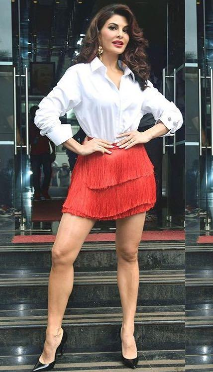 Looking for a similar red fringe skirt, white shirt and black pointed heels like Jacqueline Fernandez is wearing at the promotions of Judwaa2 on Danceplus - SeenIt