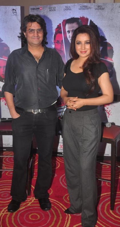 Help me find this black top with grey trousers that Tisca Chopra is wearing - SeenIt