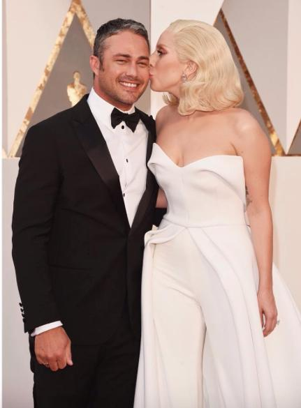 Lady Gaga in a stunning Brandon Maxwell jumpsuit kissing Taylor Kinney at the Oscars. <3 - SeenIt