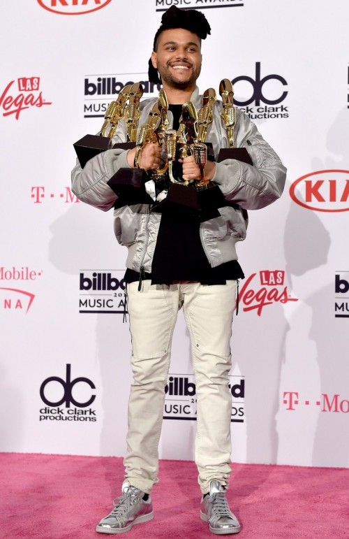 That smile says it all..The Weeknd and his 8 trophies at the BBMAs. - SeenIt