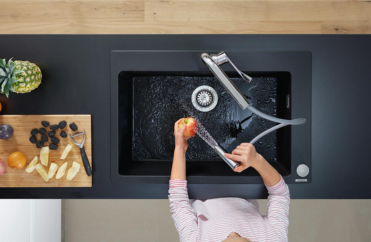 SquareRooms-hansgrohe-silicatec-granite-kitchen-sink-woman-hand-washing-apple