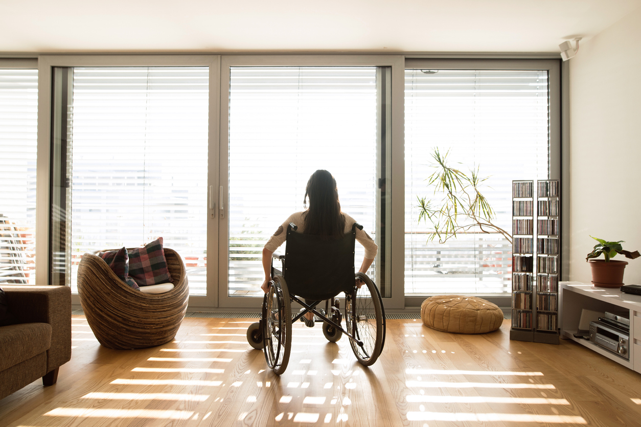 squarerooms-wheelchair-woman-living-room-window-wooden-floor