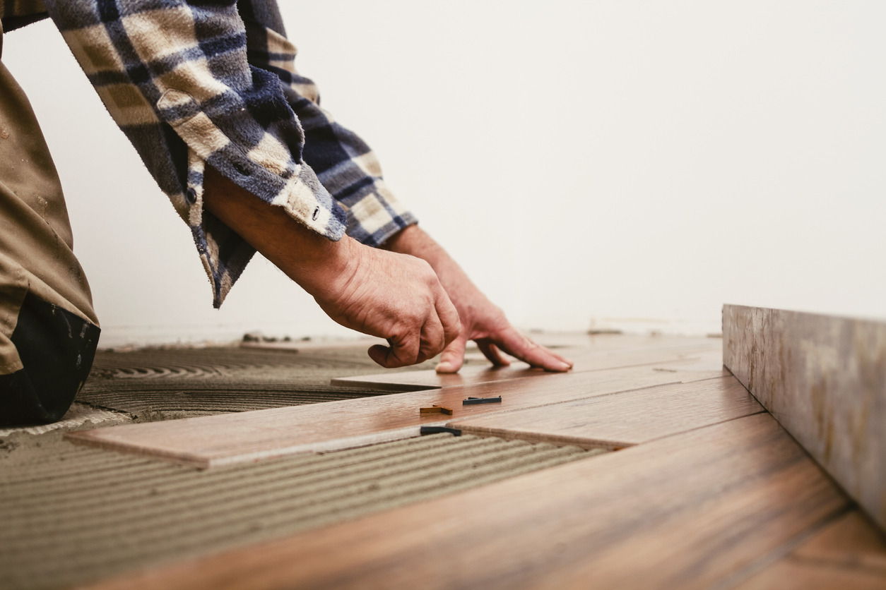 squarerooms-man-hand-placing-wooden-floorboard-on-adhesive