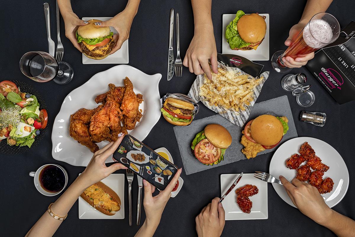 squarerooms-burger+-plus-restaurant-fast-food-flatlay-burgers-dark-black-background-fries-hands-arms
