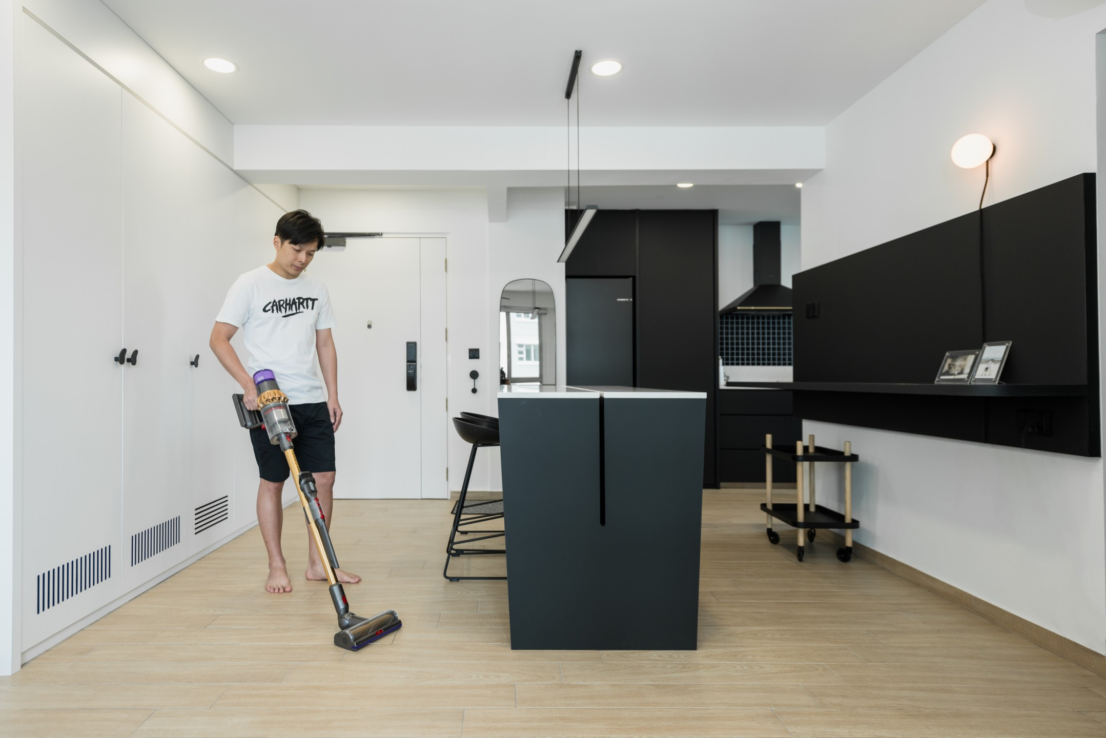 squarerooms-dyson-home-appliance-lifestyle-monochromatic-sleek-man-cleaning-vacuum-kitchen