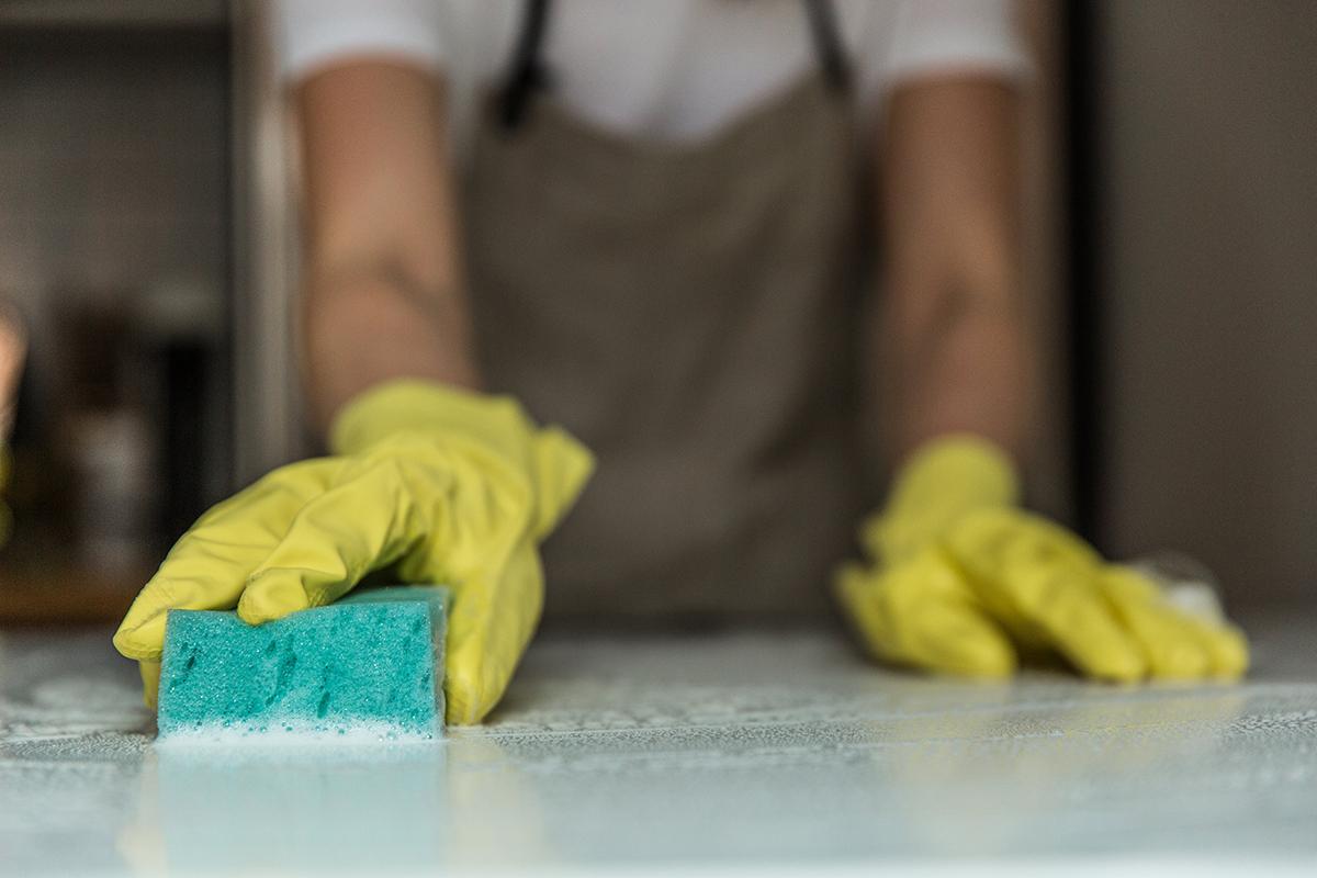 squarerooms-man-hands-sponge-cleaning-countertop-kitchen