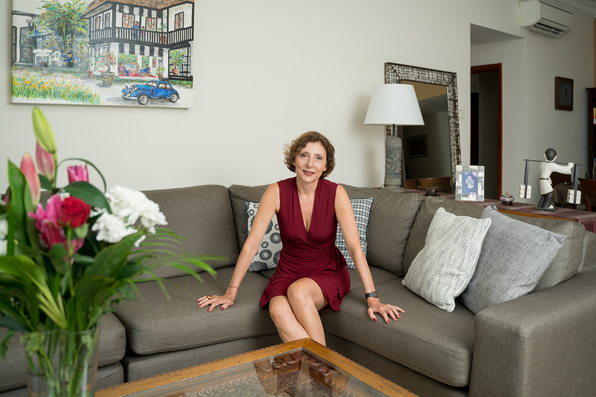 squarerooms Nathalie Ricaud from get organised and beyond woman sitting on couch in red dress