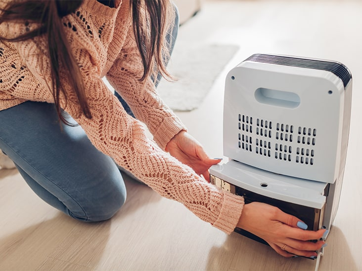 girl kneeling down to set up humidifier