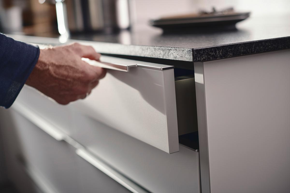 squarerooms rehau laminates kitchen surfaces modern design grey black island drawer hand arm person opening edgeband handle