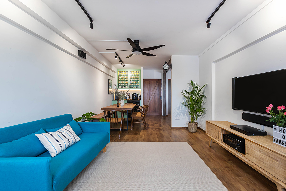 squarerooms renozone home renovation interior design makeover 4 room hdb bto flat eclectic retro vintage style jurong west blue couch living room tv console rug wood floors open concept space