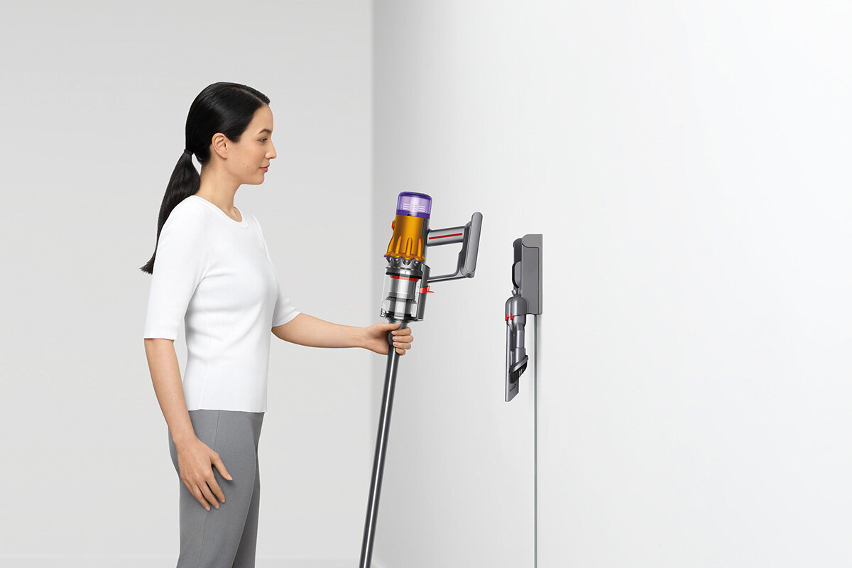 squarerooms dyson v12 detect slim total clean vacuum new launch release appliance cleaning device woman placing vacuum on charging dock station wall