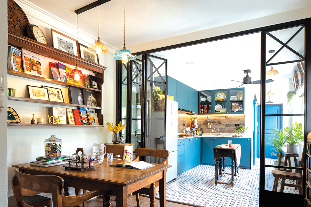 squarerooms d'marvel scale home renovation interior design makeover 3 room walk up apartment dining room clutter antiques collector maximalist maximalism kitchen blue cabinets wood table open concept clear glass door