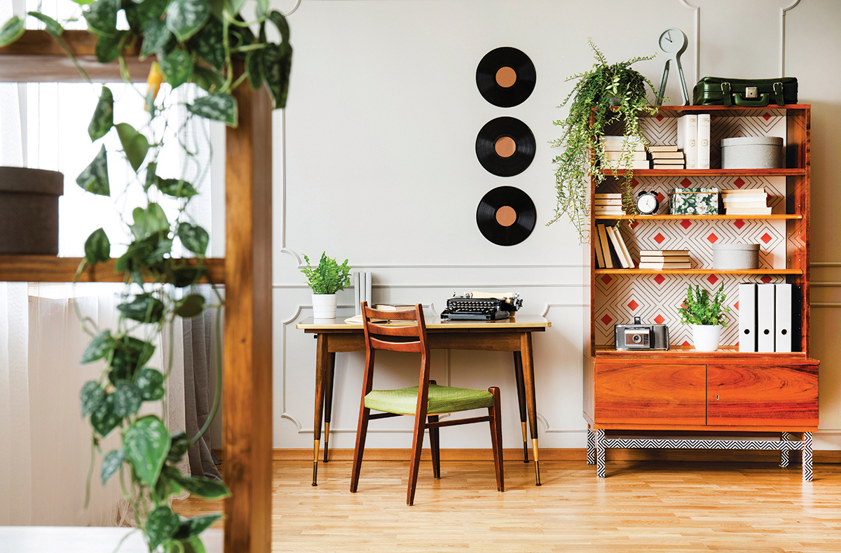 squarerooms black retro typewriter on a unique wooden desk, a mid-century modern chair and a renovated bookcase in a hipster home office interior wood scandi cosy plants