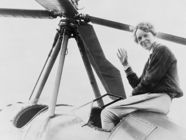 Amelia Earhart sits on her plane and waves at the camera
