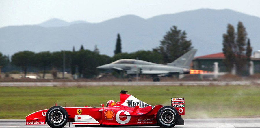 F1 legend Michael Schumacher races a Eurofighter Typhoon fighter jet.