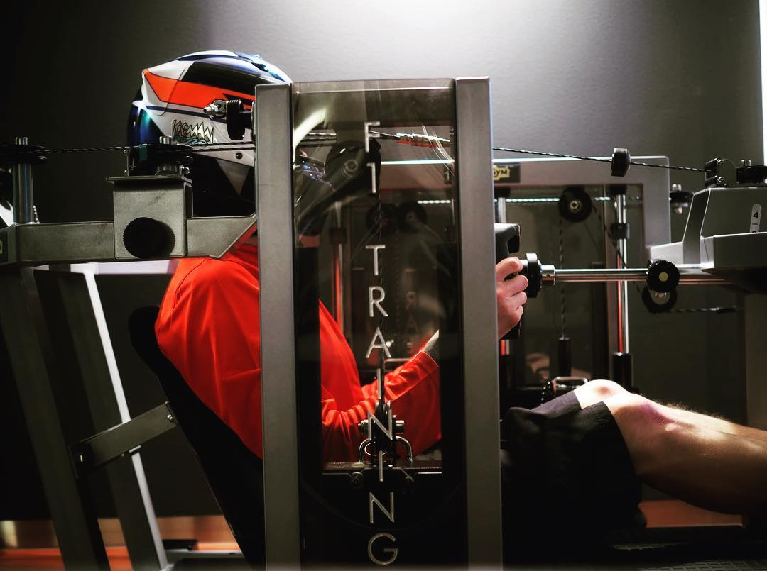 Finnish Formula 1 driver Kimi Raikkonen using a specialised machine to exercise his neck muscles.