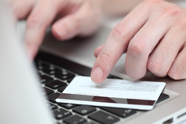 Young man's hands using a credit card for online shopping on laptop. Close-up.