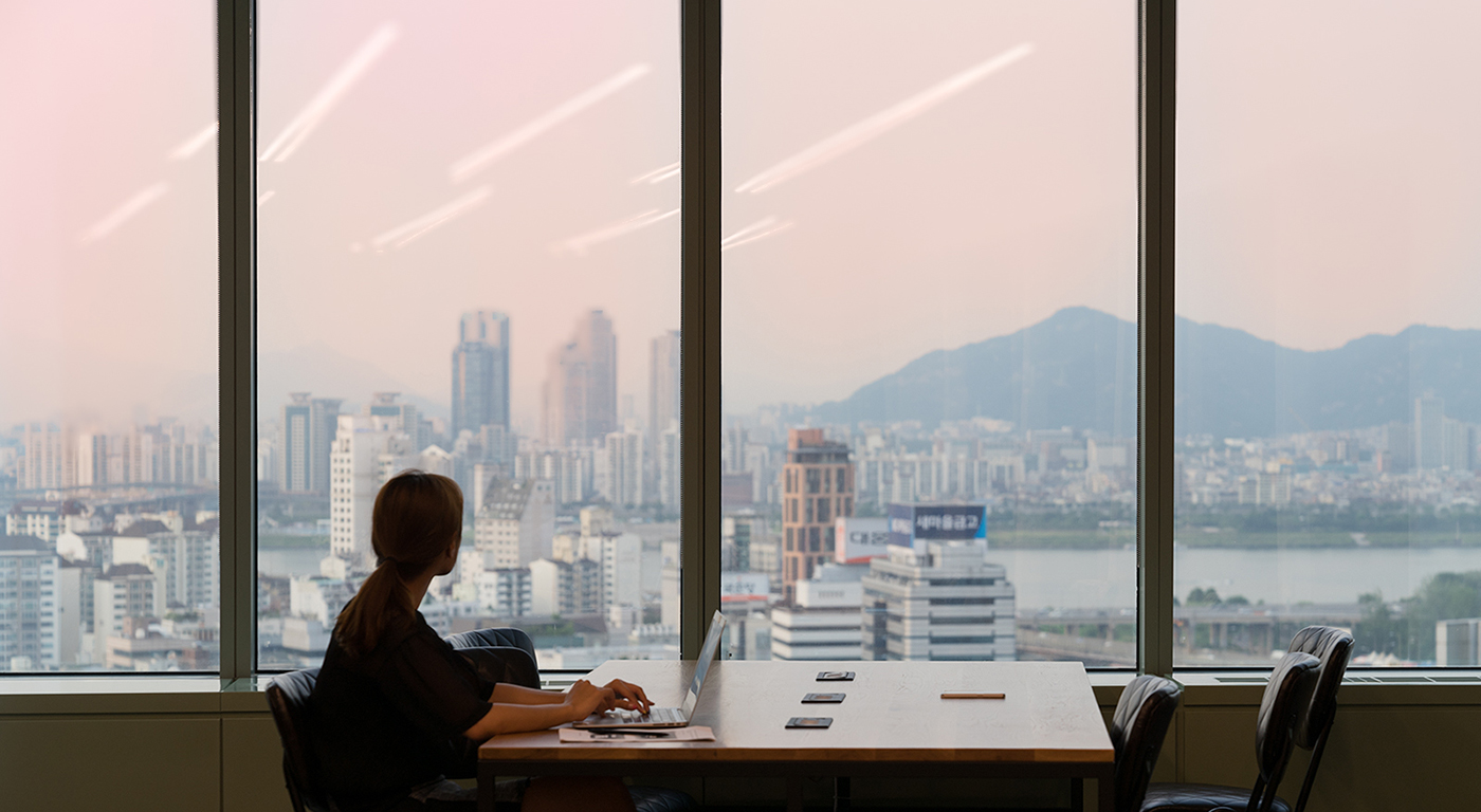 A business professional working at an office with city view