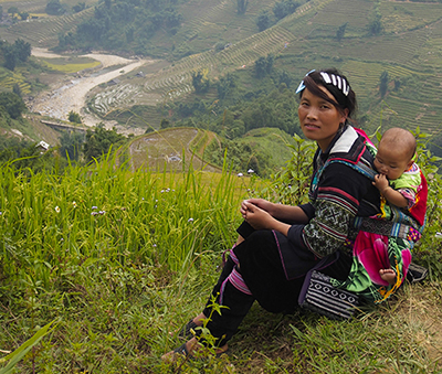 A H'mong mother and child resting on the way back to the village