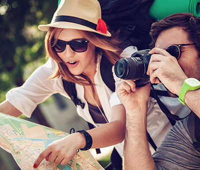 Two travelers; one consulting a map and the other taking photos