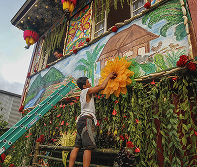 A local decorating his house during the Pahiyas Festival in Lucban