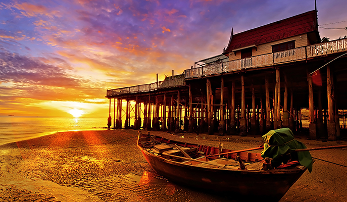 A fishing boat on Hua Hin beach at dawn
