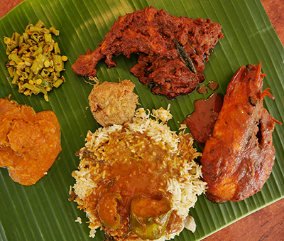 Chicken, prawn, battered fish cutlets and stewed pumpkin come with their own dressing of curry in this typical South Indian banana leaf meal