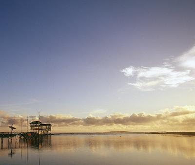 The Philippines, Surigao del Norte, Siargao Island, morning silhouette of a surfer on the Cloud 9 pier