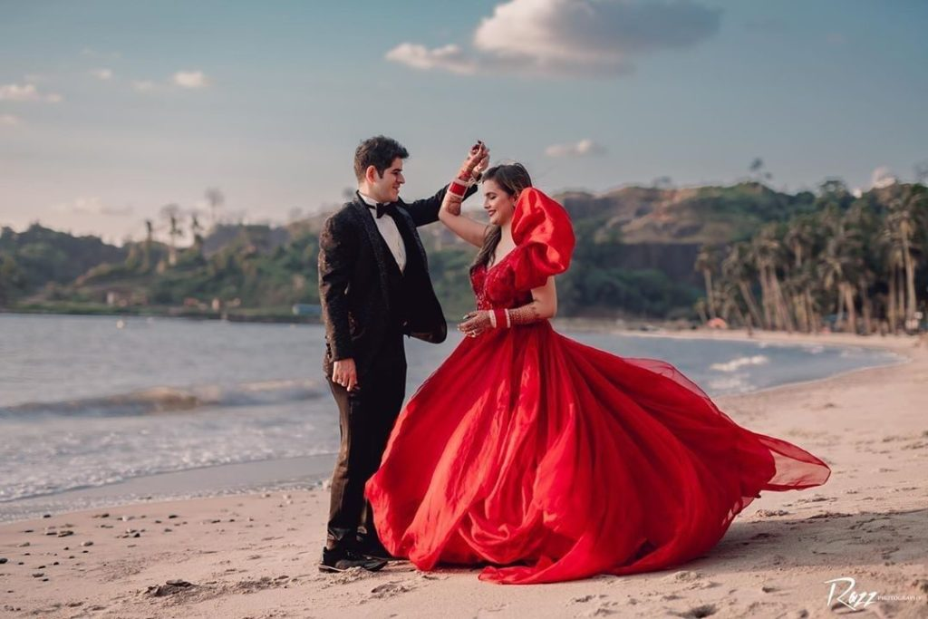 Bride in red gown & groom in black tuxedo