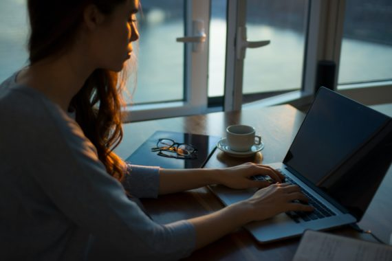 Woman typing on laptop beside window in the evening