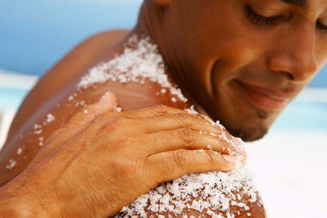 Hand Rubbing Bath Salt on Man's Shoulder --- Image by © Dylan Ellis/Corbis