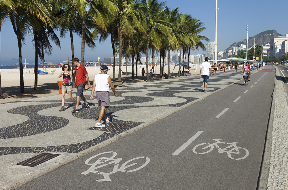 Rio de Janeiro, Brazil - June 2nd, 2013: One man drives a bicycle in the bike path located between Copacabana Beach famous sidewalk and Atlantica Ave. People walk in the sidewalk.
