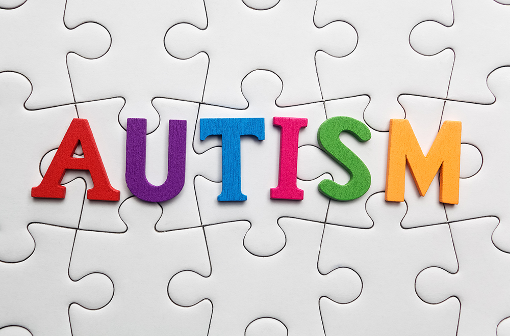 Autism inscription on a white puzzle background. Symbol of autism.