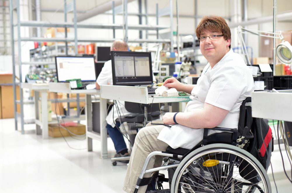 handicapped worker in a wheelchair assembling electronic components in a modern factory at the workplace