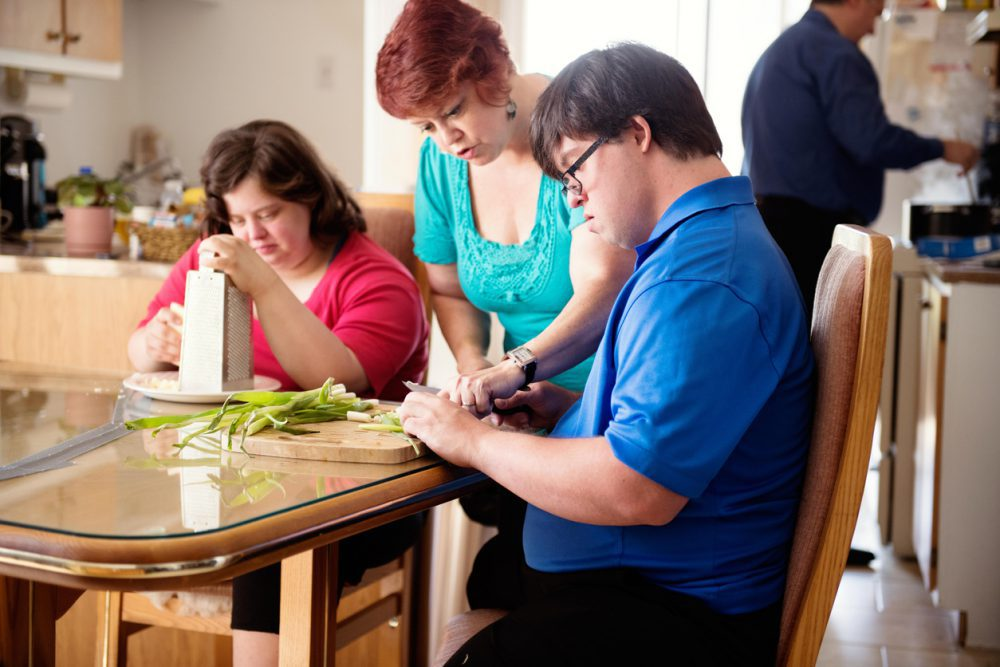 Couple in love of 26 years old Down Syndrome at her apartment in Montreal. They are learning to live in an apartment independently. They are cooking together.  the young men cutting vegetables. The mother in law show him how to do. Color and horizontal photo was taken in Quebec Canada.