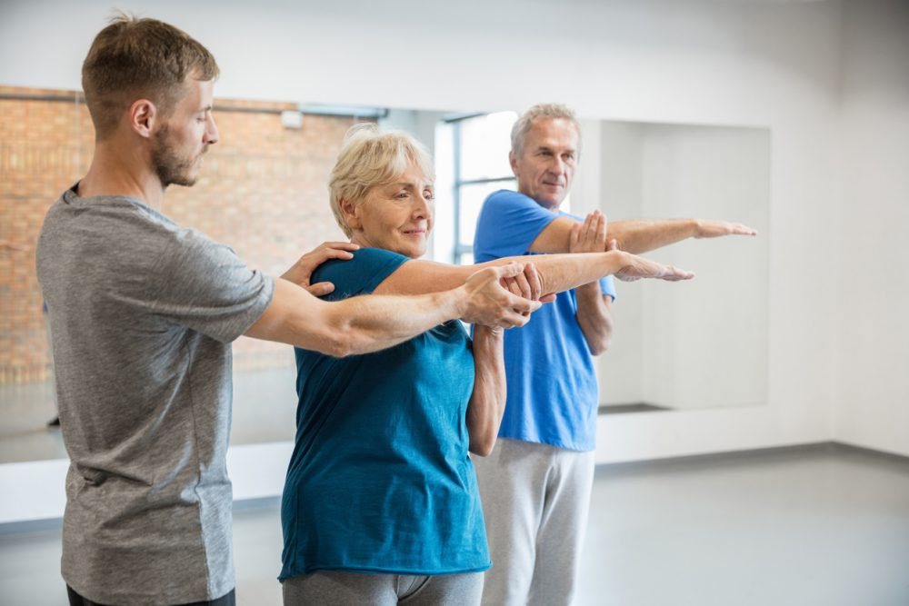 Senior people exercising with trainer at rehab club