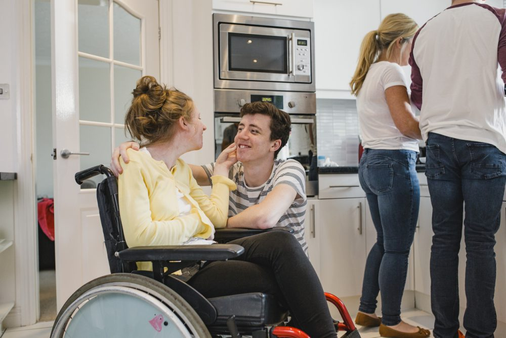 Teenager Playing with Disabled Sister at Home