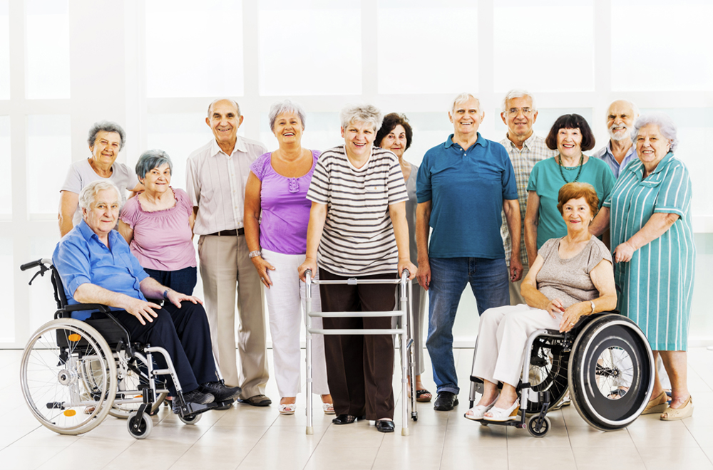 Large group of cheerful seniors looking at the camera. Some of them have psychical impairment.