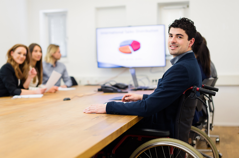 business team having a meeting in a modern office. one man is sitting in a wheelchair.