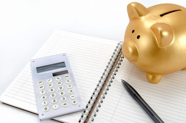 金色の豚の貯金箱と電卓とノート